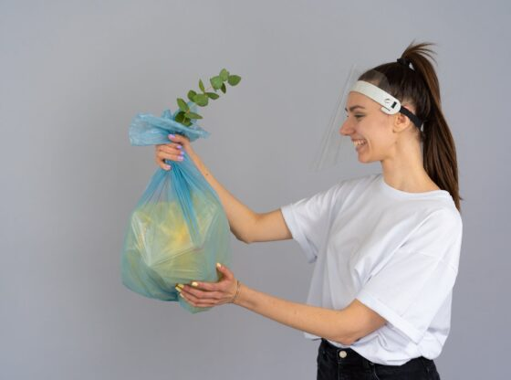 woman in white crew neck t shirt holding green plastic bag